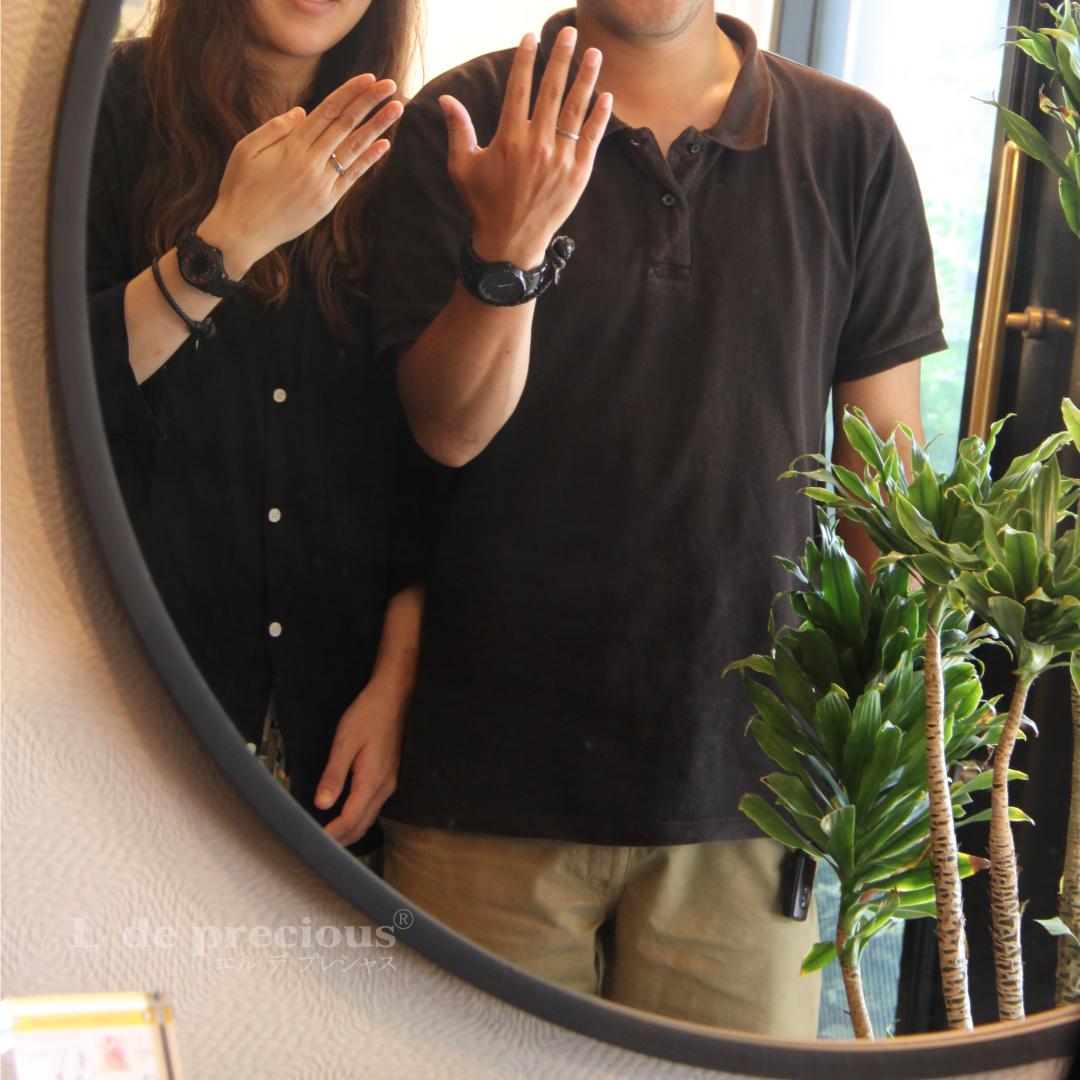 カップルが鏡の前で結婚指輪の試着をしています。