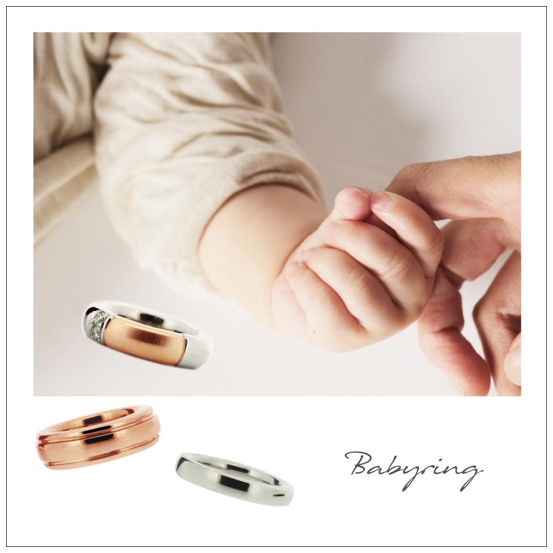 お母さんの指をにぎった赤ちゃんの手とベビーリング。