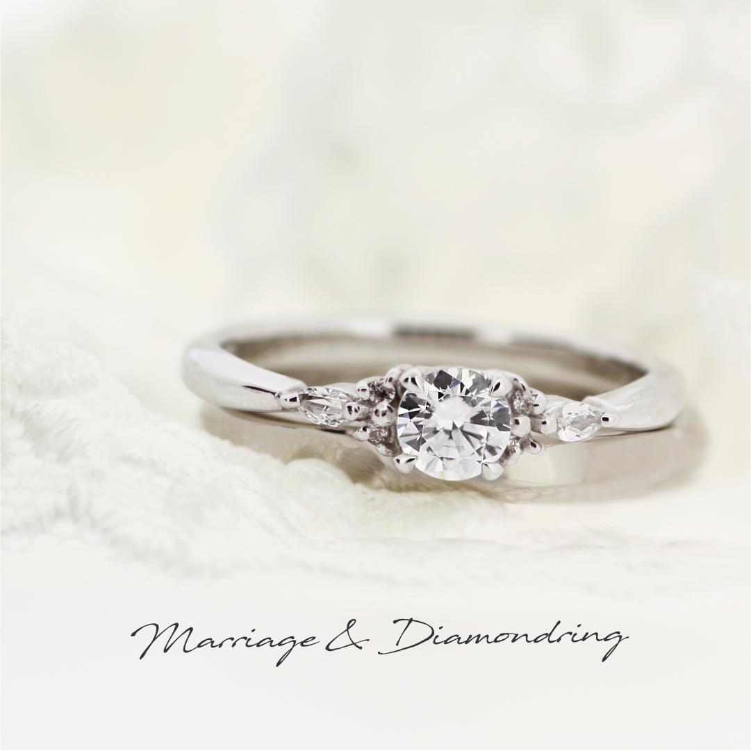 マーキスカットの脇石がついたプラチナの婚約指輪と、シンプルなストレートラインのブラックゴールドの結婚指輪です。