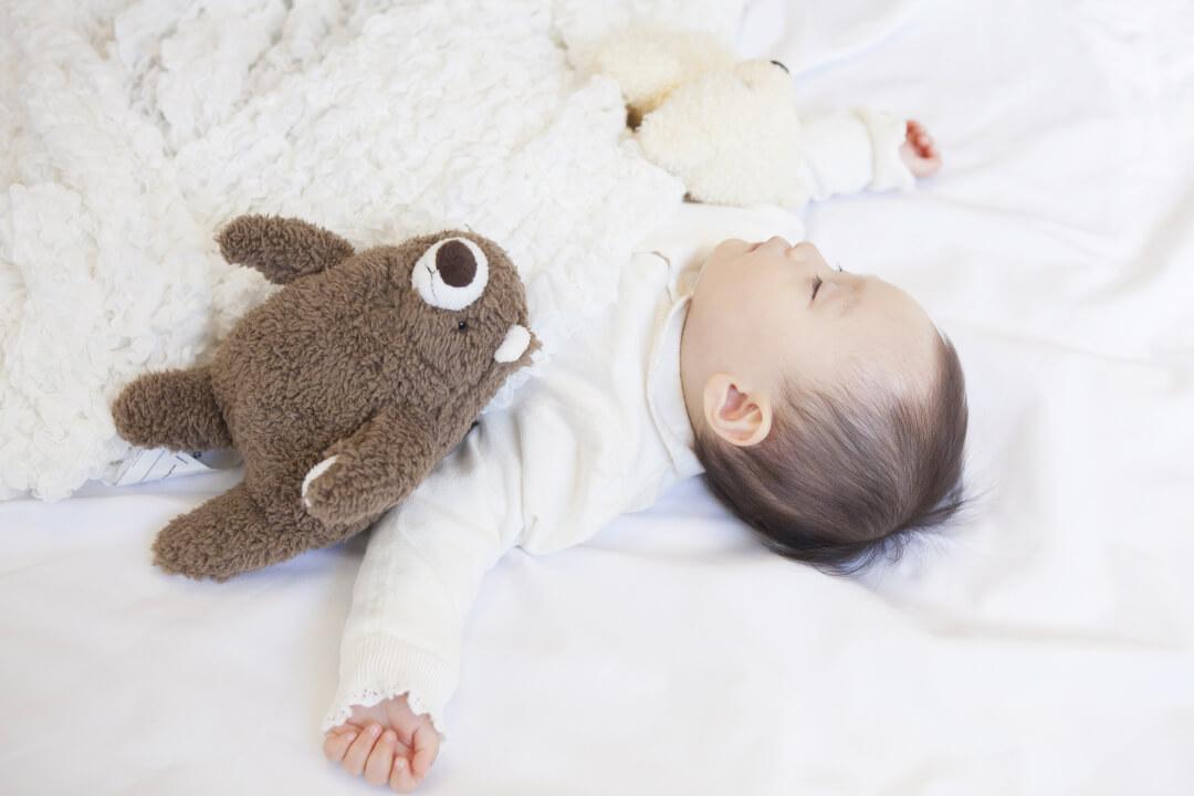 クマのぬいぐるみと一緒に寝ている赤ちゃん