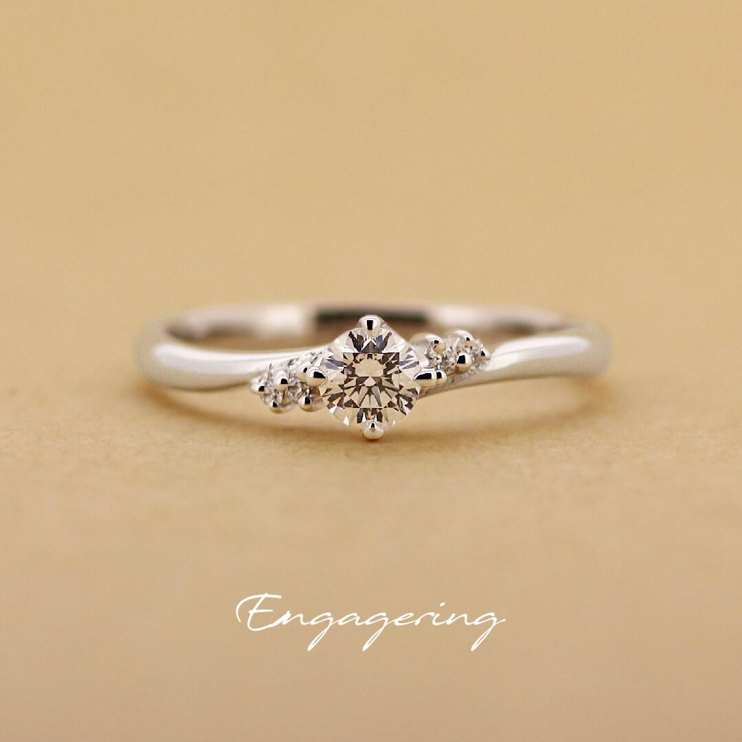 センターダイヤの両サイドに2ピースずつ脇石がついた、ウエーブラインの婚約指輪です。