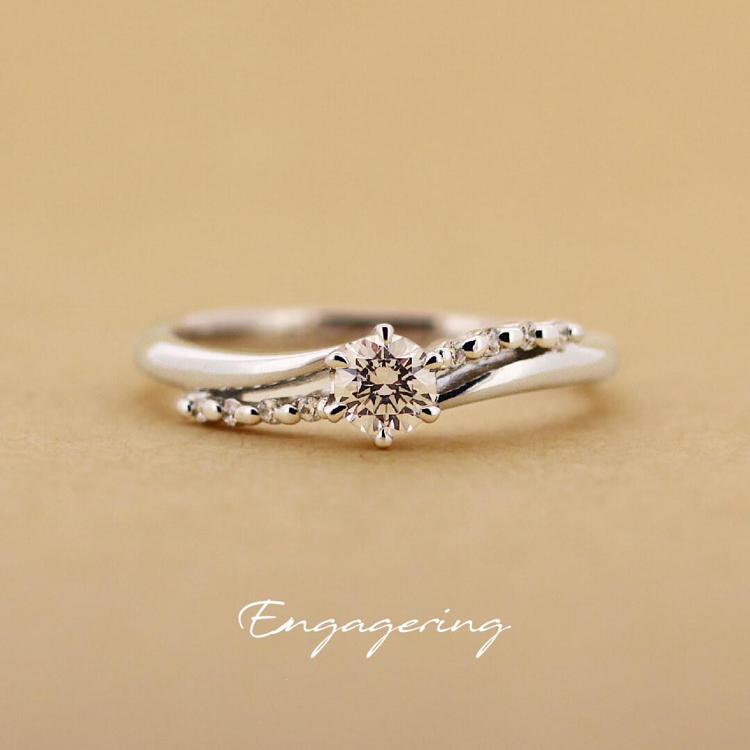 ウエーブラインに沿ってメレダイヤを爪で留めた、透かしのあるデザインの婚約指輪です。