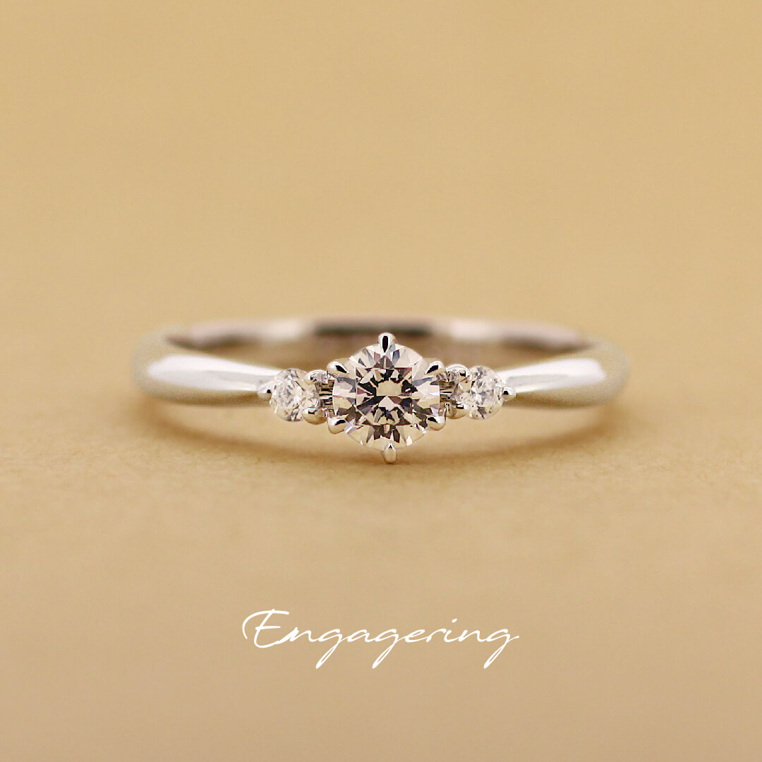 センターダイヤの両サイドにぴったりと2ピースずつ脇石を留めた、ストレートラインの婚約指輪です。