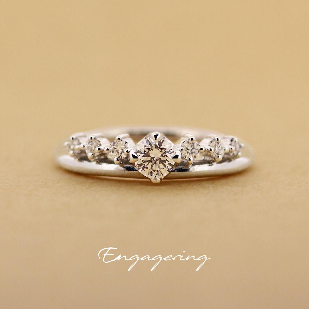 センターダイヤの両サイドに並んだ大きめの脇石がティアラのようにも見える、ストレートラインの婚約指輪です。