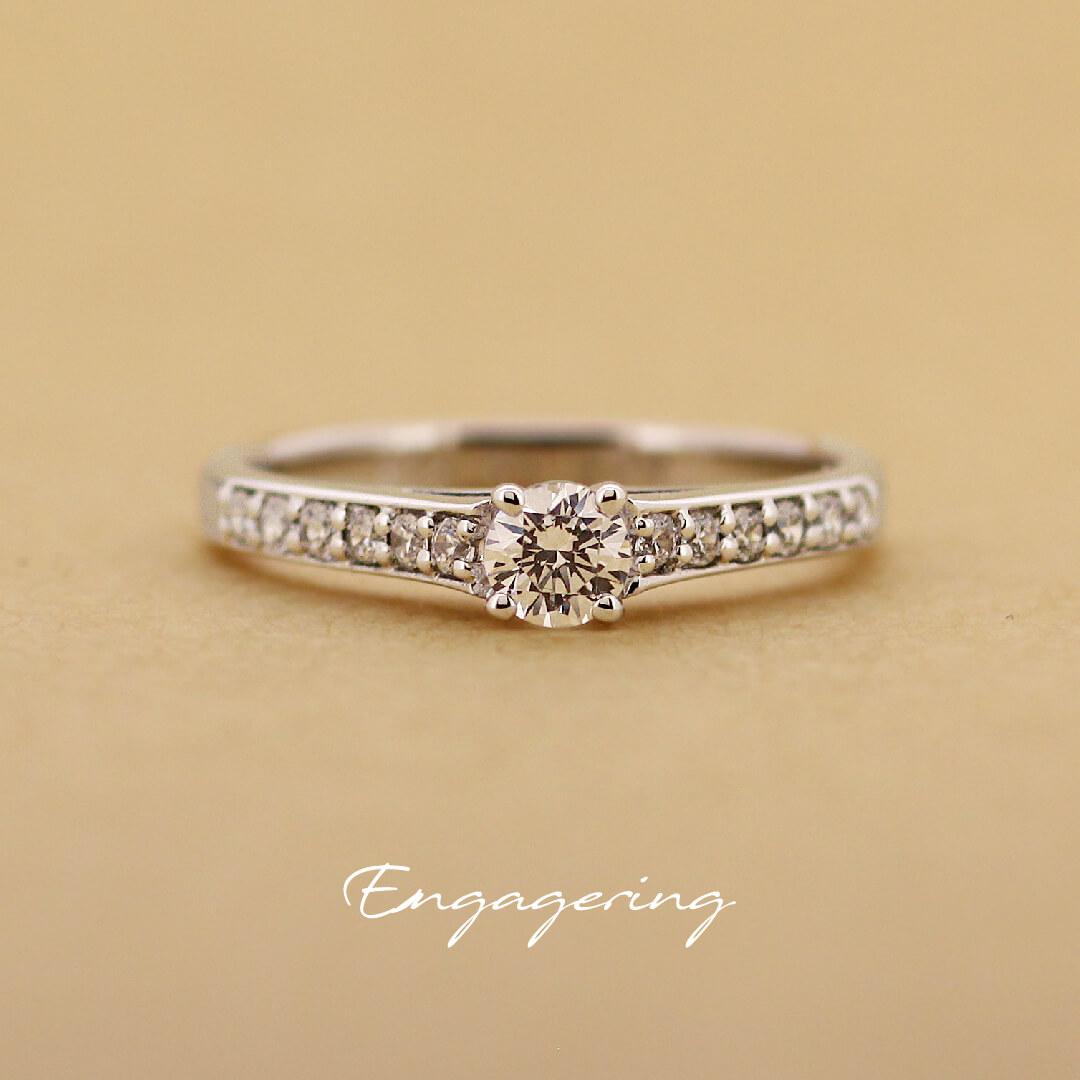 センターダイヤの両サイドにメレダイヤを並べた、エタニティ風のストレートラインの婚約指輪です。