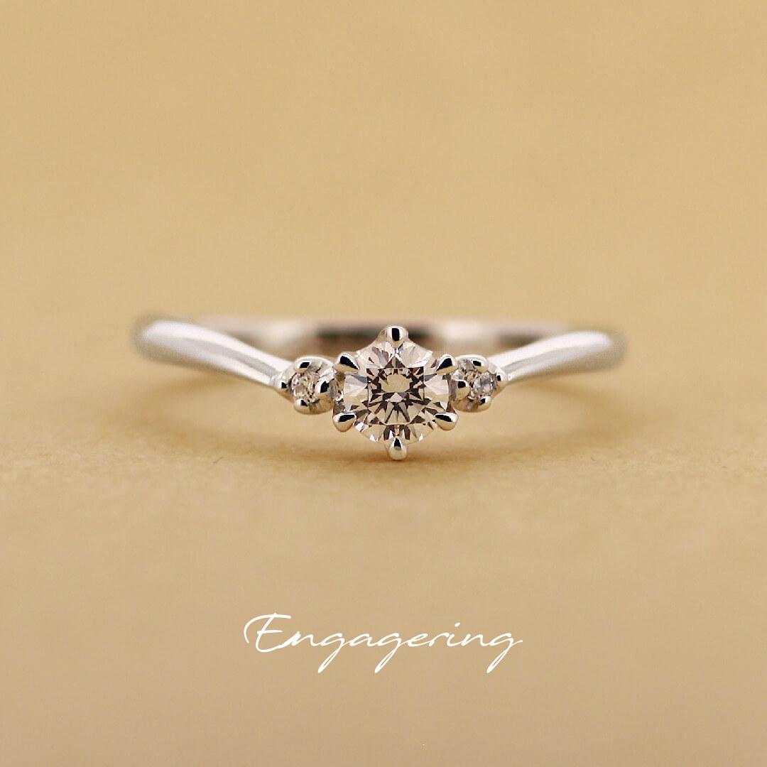 センターダイヤの両サイドに脇石を1ピースずつ留めた、ブイラインの婚約指輪です。