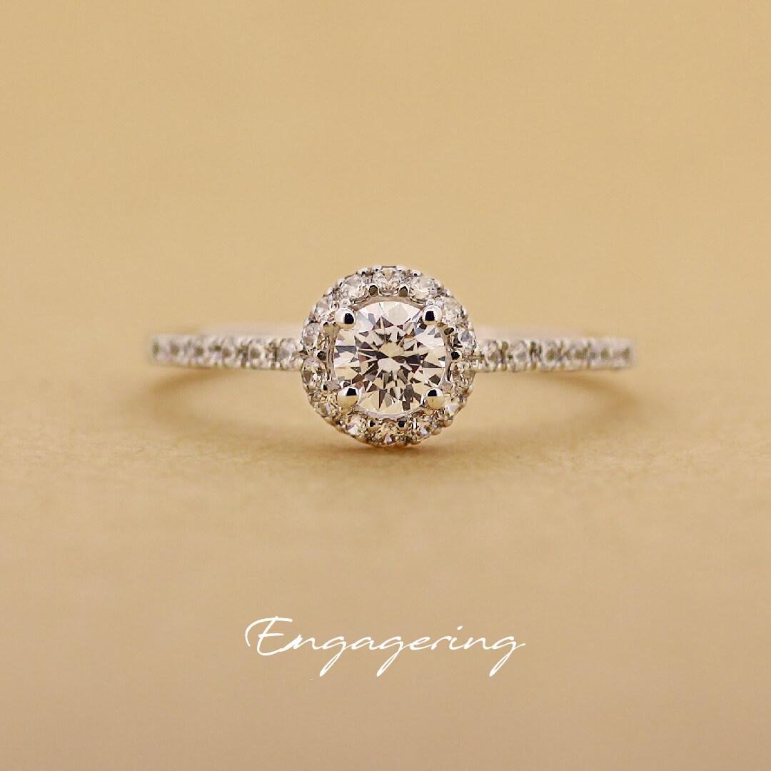 センターダイヤをメレダイヤで丸く囲み、細みのアームにもメレダイヤを並べたストレートラインの婚約指輪です。