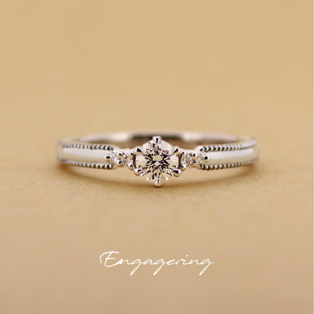 センターダイヤの両サイドに1ピースずつ脇石を留め、アームには細かなミル打ちが入った、ストレートラインの婚約指輪です。