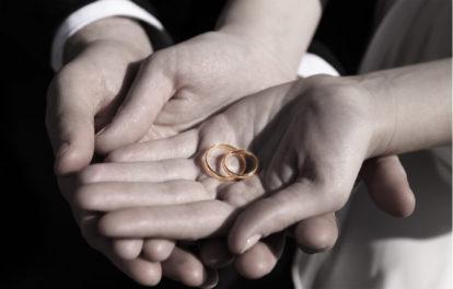 新郎新婦がふたりで大切にゴールドの指輪を持っています。