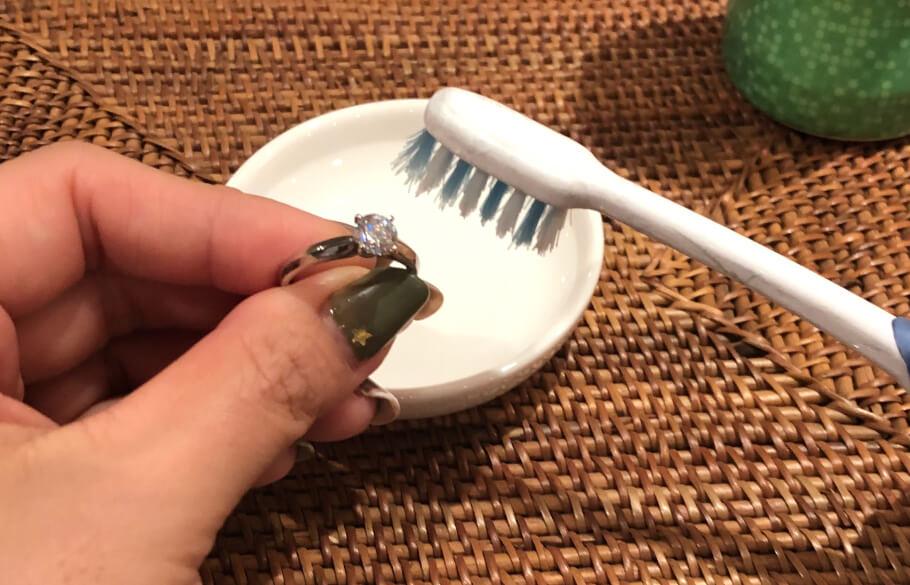 指輪を歯ブラシでこすっている様子