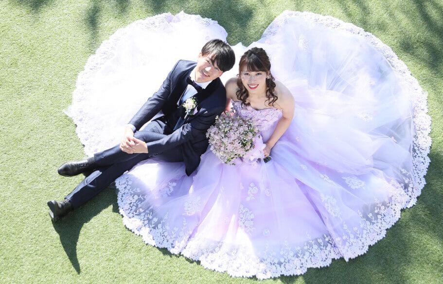 芝生に座って上を見上げて微笑んでいるタキシードとドレスを着たカップル
