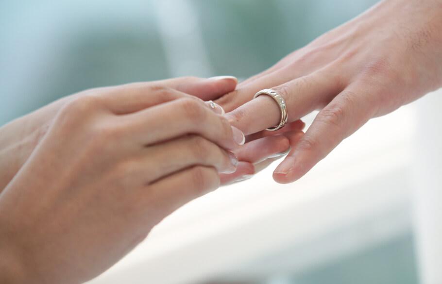 女性が男性の左の薬指に結婚指輪を入れている