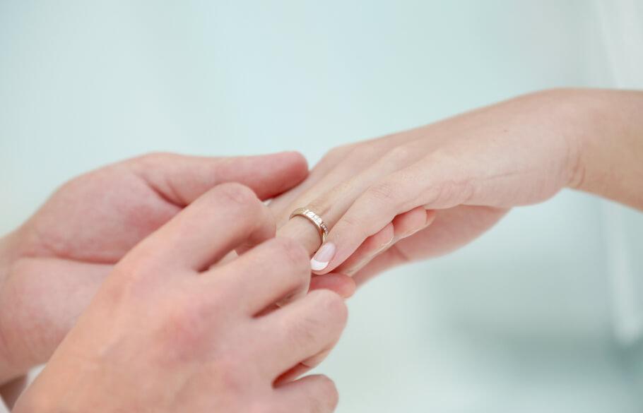 男性が女性の左の薬指に結婚指輪を入れている